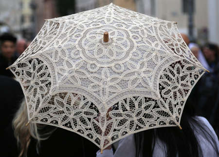 doilies: vintage umbrella all hand-decorated with lace doilies and two women Stock Photo