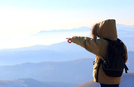 wench: outstretched arm and pointing finger of young person with backpack in the mountains