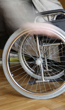 dystrophy: motion of hand of the young disabled in the wheel of the wheelchair