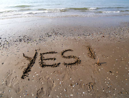 Great YES written on the sand of the sea