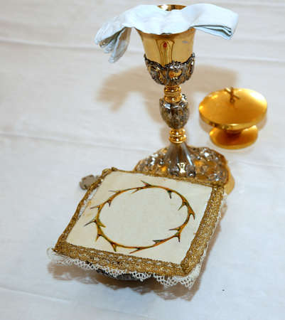 clergy: Golden Chalice with wine in the altar of a Christian Church during Holy Mass Stock Photo