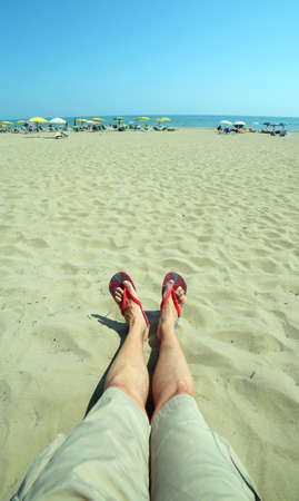 footware: young adult with long legs and flip flops at the foot rests on the beach during the summer holidays
