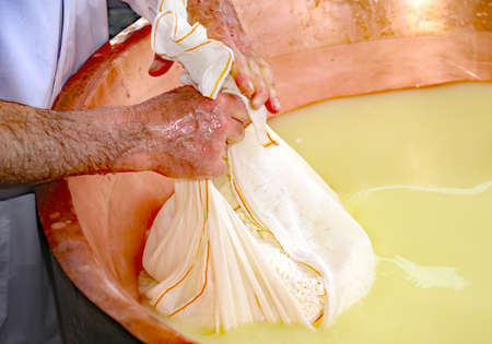 herdsman: herdsman Cheesemaker collects cheese from the big copper cauldron with cows milk and goats milk