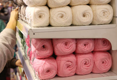 many balls of wool for sale on the shelf in the shop of importers of fabrics and wool