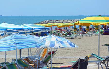 sun umbrellas: sun umbrellas in the warm sandy beach of the tourist village and Pier on the horizon