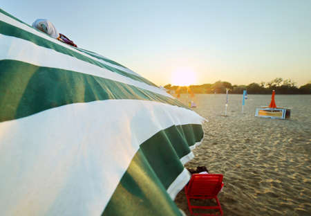 repose: back lit sun umbrellas with sunset in the summer on the beach