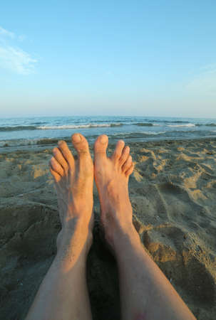 nudist: two bare feet of a man on the sandy beach at sunset