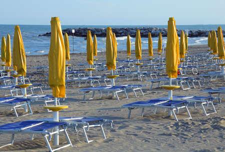 sun umbrellas: Yellow closed Sun umbrellas with sun loungers and deckchairs Stock Photo