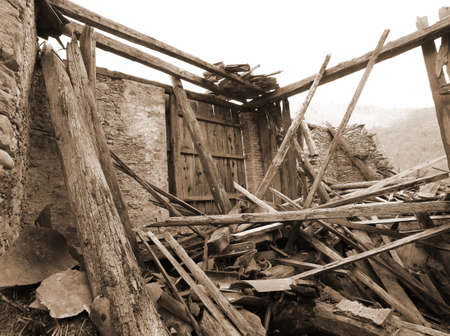 cataclysm: wooden planks and rubble and the ruins of the house completely destroyed by powerful earthquake