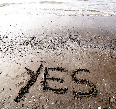 Big YES written on the sand of the sea