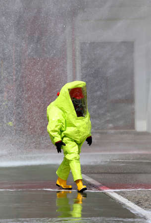 nuclear waste disposal: man with yellow protective gear against biological risk Stock Photo