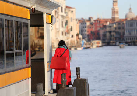 natty: elegant young woman dressed in red with red purse awaits boat on the Grand Canal in Venice Italy Stock Photo