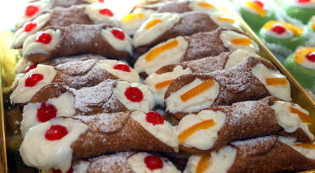 many Sicilian cannoli with custard and cherries or candied fruit
