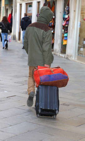 duffel: Vagabond with suitcase luggage trolley in calle of Venice in Italy