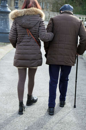 generational: caring daughter walks with elderly father with stick in the city Stock Photo