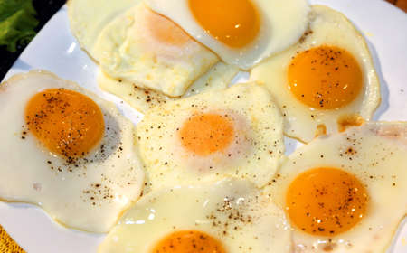 peppery: fried eggs with red yolk with a sprinkling of pepper over Stock Photo