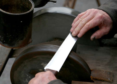 Elder grinder with hands sharpen a blade