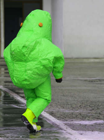 chemical warfare: man with green protective gear against biological risk Stock Photo