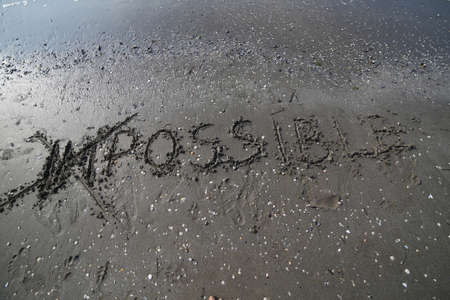 IMPOSSIBLE written with the letters IM cancelled in the wet sand of the beach Banco de Imagens