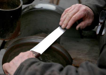 sharpen: Elder grinder with large hands sharpen a blade of a knife