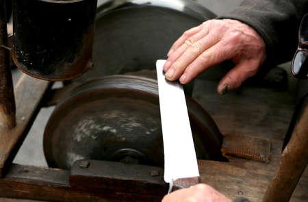 sharpen: Elder grinder with large hands sharpen a knife