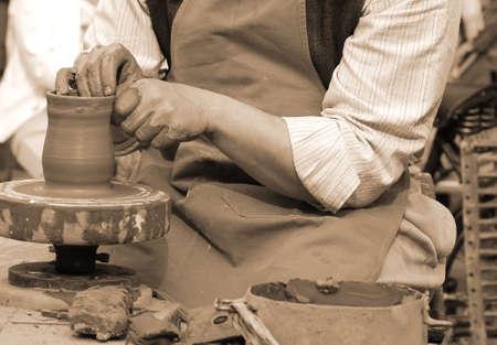 potter: craftsman potter shaping clay to make an handmade pot
