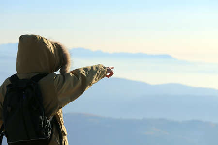 occurred: young Explorer with winter jacket with hood and black backpack indicates the horizon from above the top of the mountains