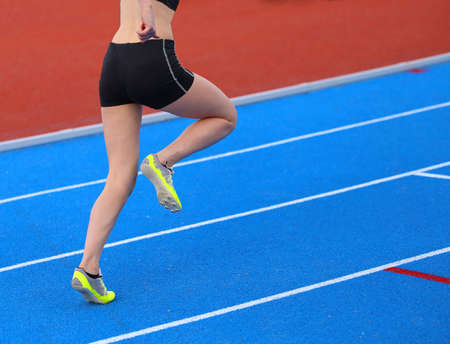 athletics track: young woman running on the athletics track