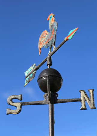 puntos cardinales: ancient weathervane with cock above an arrow and the four cardinal points North East West South