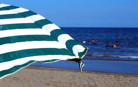 foreshore: beach umbrella with swimmers splashing in the sea in summer