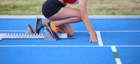 starting blocks: athlete in the starting blocks of a athletic track before the start of running race