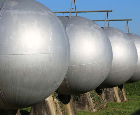 production area: many giant gas pressure vessels for the storage of flammable natural gas in the restricted area of the fuel production refinery