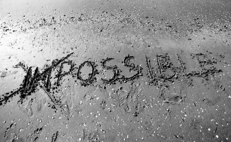 IMPOSSIBLE written with the letters IM cancelled in the wet sand