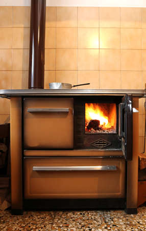 wood burner: wood-burning stove in the kitchen of mountain home