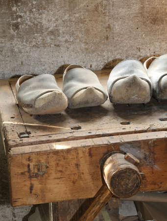 clogs: many Wooden soled type dutch clogs and a wooden vise Stock Photo