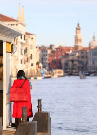 natty: elegant woman dressed in red with red purse awaits vaporetto on the Grand Canal in Venice Italy Stock Photo