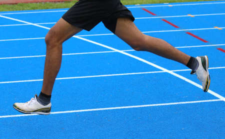 athletics track: long legs of fast runner runs into the in athletics track