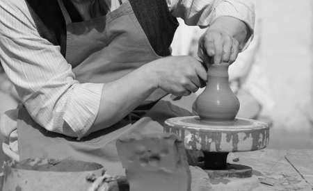 alfarero: alfarero experto que trabaja con el torno que hace un crisol de arcilla Foto de archivo