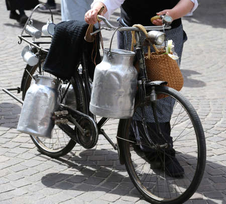 milk cans: elderly woman with old bicycle and aluminium milk cans