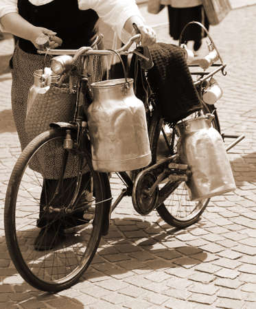 milk cans: elderly woman carrying milk cans with a old rusty bicycle