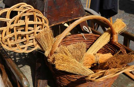 sorgo: escobas de sorgo, un sacudidor de alfombras y artículos de mimbre envases para la venta en el mercado de pulgas Foto de archivo