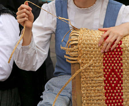 tapering: young girl with tapering fingers of the hand creates patiently a straw bag on the road