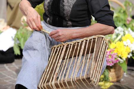 trabajo manual: manos de una mujer mayor, mientras que la torcedura de la paja para crear un bolso de paja hecho a mano