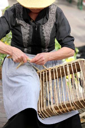 trabajo manual: anciana con sombrero de paja crea una bolsa Foto de archivo