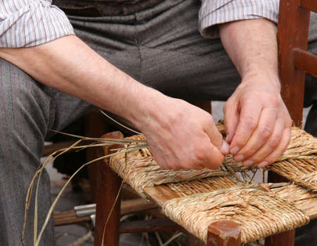 repairer: hands of a mender of chairs while repairing an old wooden chair with straw
