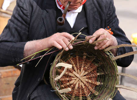 trabajo manual: Hombre mayor fumando su pipa crea una cesta de paja