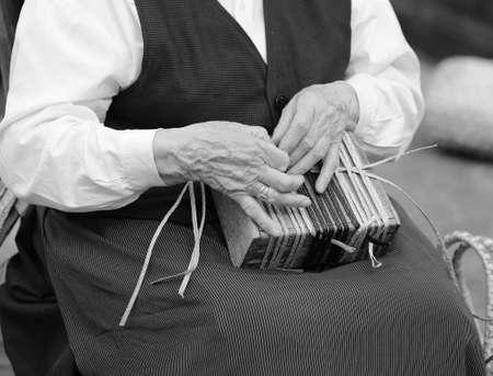 trabajo manual: manos de una anciana mientras se crea una pequeña bolsa de paja Foto de archivo