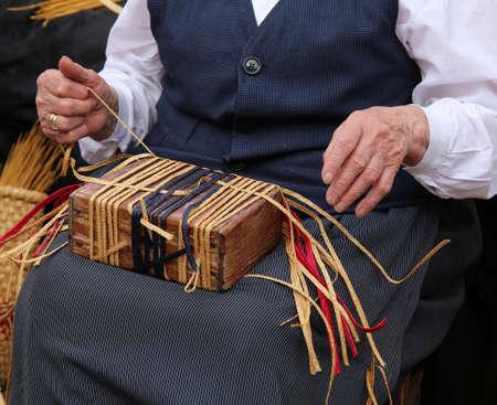 trabajo manual: manos arrugadas de una anciana mientras torcer la paja para crear un bolso de paja hecho a mano
