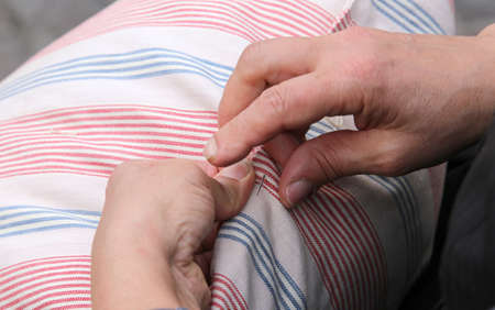 darning needle: hands of a woman while sewing with needle and thread the old pillow Stock Photo