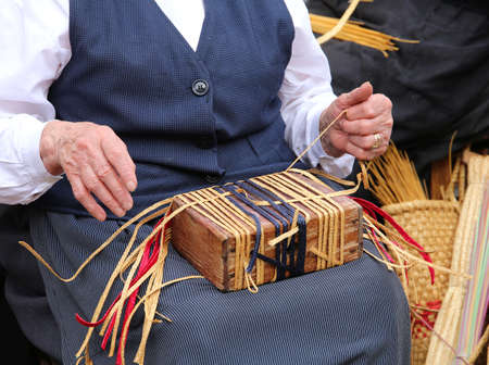 trabajo manual: hands of an elderly woman while creating a straw bag